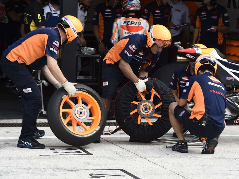 Engineers changing the wheels on a bike pre-qualifying